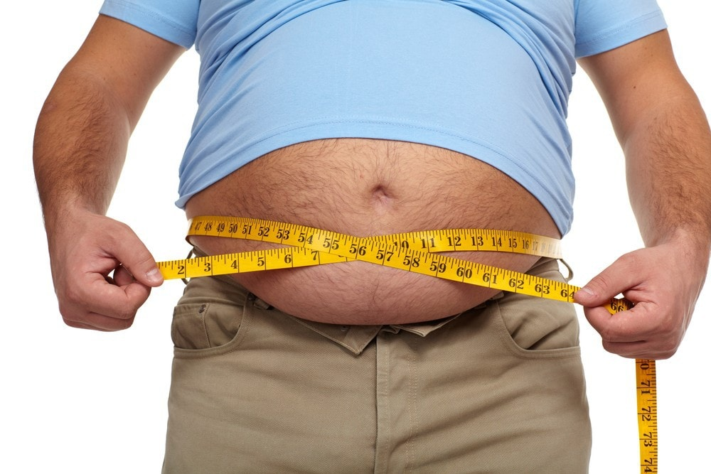 Image of fat man measuring belly